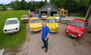 Hobby vintage vehicle restorer Lewis Buchan with some of his 11 three-wheeled vehicles. DCT Media/Kenny Elrick