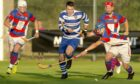 Newtonmore's Steven Macdonald is challenged by Kingussie's James Falconer in a Mowi Premiership tie from 2019.