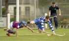 Kingussie's James Falconer, left, tangles with Craig Ritchie (Newtonmore).