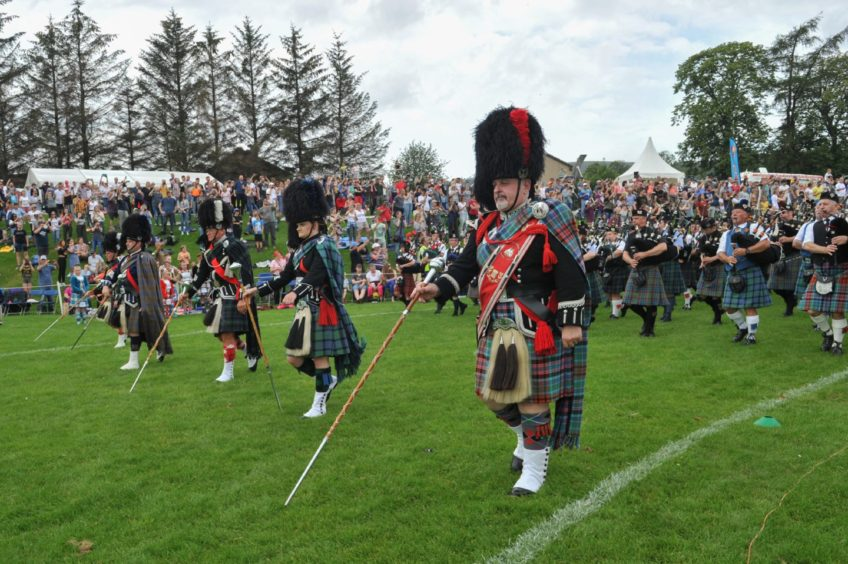 Dufftown Highland Games 2019. Picture: Chieftain Alex Grant marches with his three daughters with Dufftown pipe band. Pictures by Jason Hedges