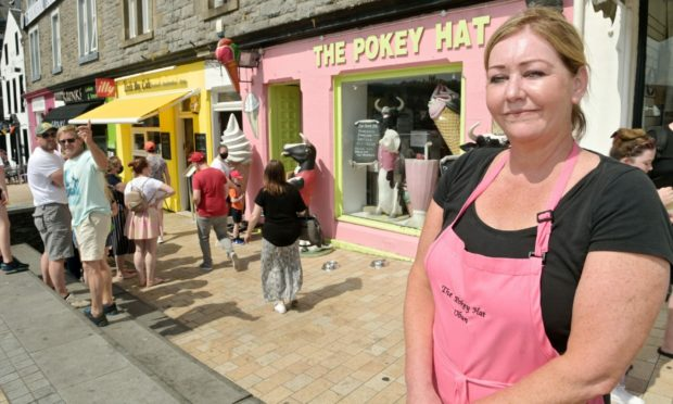 Business owner Rosanne Mackenzie as customers form a queue in the hot sun. Picture by Sandy McCook