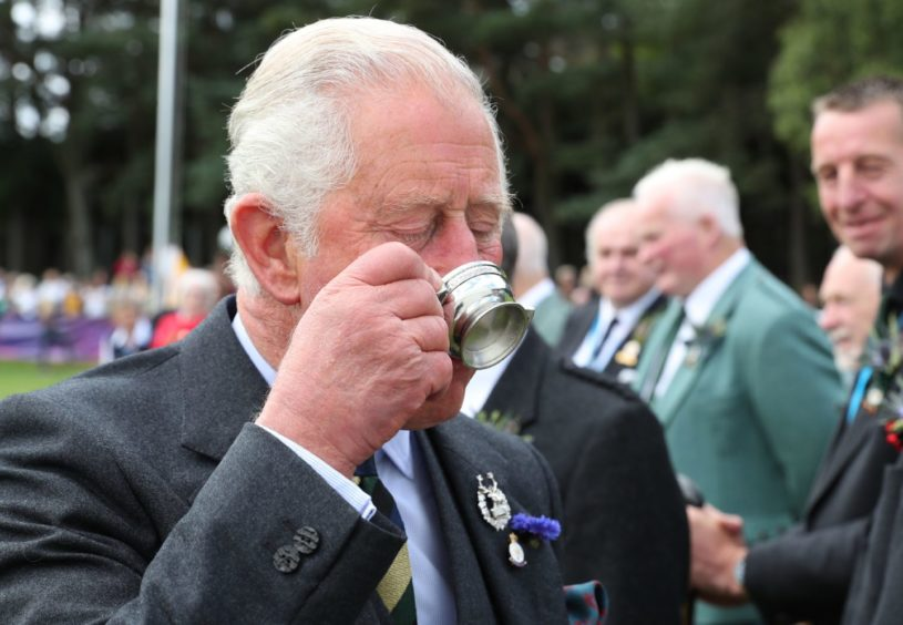 The Prince of Wales, known as the Duke of Rothesay while in Scotland, tries a whisky given to him by Clan Farquharson President Alan Caig, during his visit to the Ballater Highland Games in Monaltrie Park. Supplied by PA.