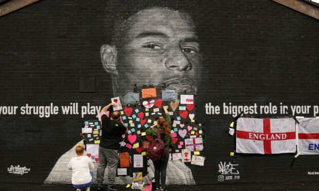People place messages of support on top of bin liners that were taped over offensive wording on the mural of Manchester United striker and England player Marcus Rashford. Photo: Martin Rickett/PA Wire.