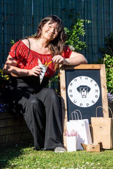 Toni Gordon sitting next to a Mother Pupper sign holding her vegan dog treats