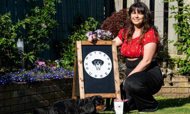 Toni Gordon of Mother Pupper vegan dog treats posing next to a company sign