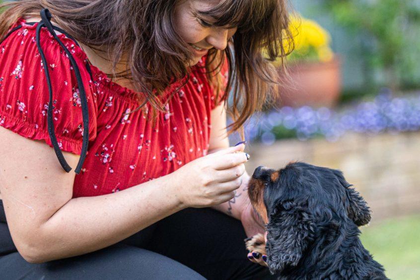 Toni Gordon feeding her dog
