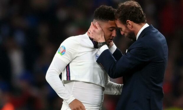 England football manager Gareth Southgate (right) comforts player Jadon Sancho