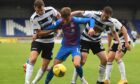 Caley Thistle's Roddy MacGregor (centre) competes with Ayr United's Aaron Muirhead (left).