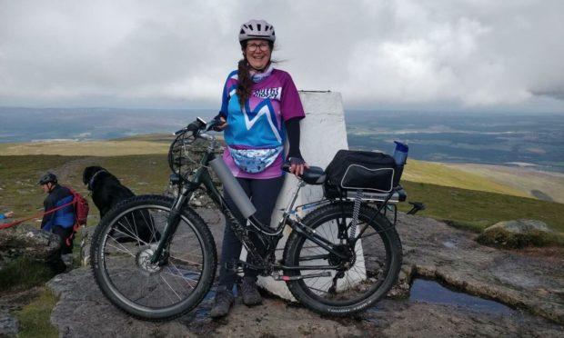 Karen Cox at the summit of Ben Rinnes with her electric bike. Photo: Karen Cox