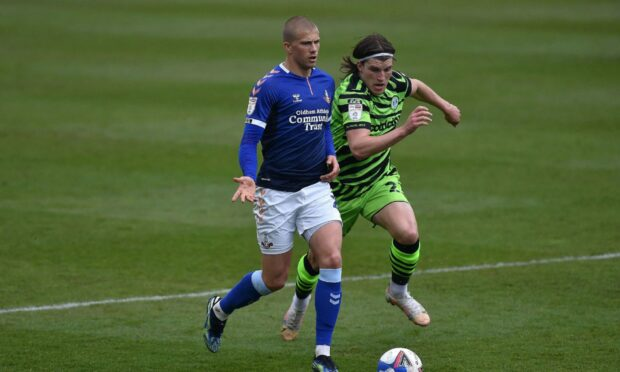 Harry Clarke, on loan for Oldham last year, tussles with Josh Davison of Forest Green Rovers.