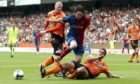 Dundee United's Lee Wilkie slides in to stop Lionel Messi. This time.