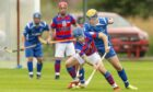 Kingussie's James Falconer tries to get away from Dylan Monk of Kilmallie.