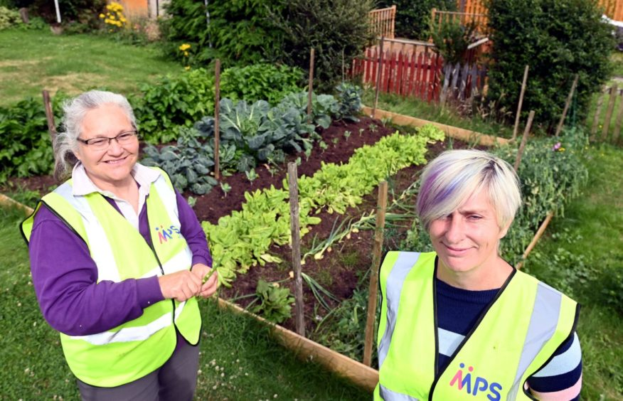 Julie-Ann Henderson (left) is teaching Emma Wood how to grow vegetables.