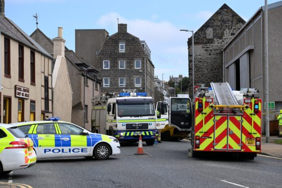 The overturned car, seen behind the Marine Aquarium sign, at the scene earlier. Car accident in Macduff near harbour close to filming of 'The Crown'  unlikely to be connected with the filming  Picture by Paul Glendell