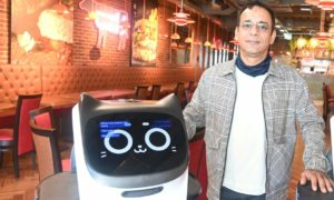 Owner Sunny Bhatti with the two robot waiting staff.