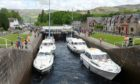 Visitors watch yachts climb the locks of the Caledonian Canal at Fort Augustus.