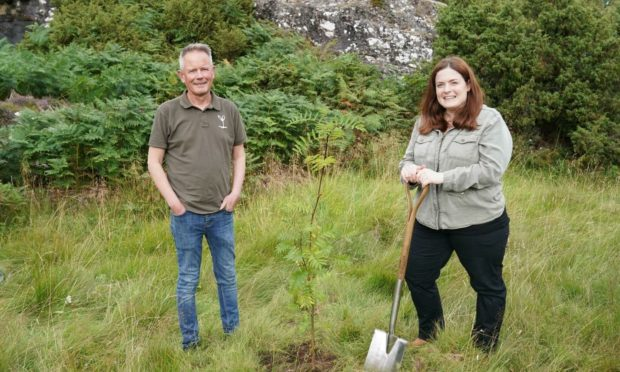 Steve Micklewright, chief executive of Trees for Life and Laurelin Cummins-Fraser, Dundreggan Rewilding Centre Director, plant a rowan tree at the centre. Picture by Ashley Coombes
