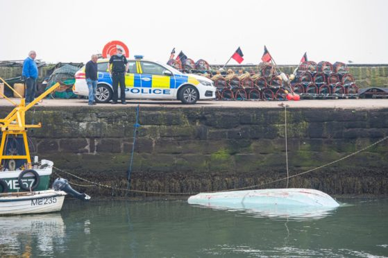 A police car sits on the quayside guarding the boat after it was returned to Gourdon harbour.