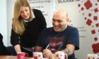 A man being helped by a staff member of Poppyscotland