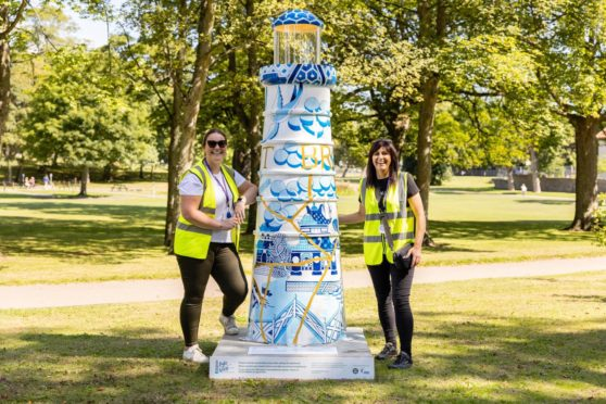 Clan's Fiona Fernie and Diane McDonald in Westburn Park with a stunning lighthouse that was sponsored by Subsea 7 and created by Celie Byrne.