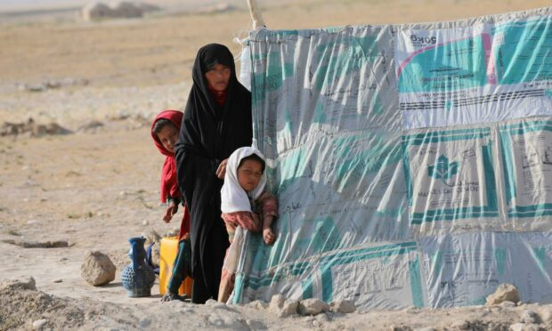 An internally displaced Afghan woman stands with her daughters in front a makeshift tent (Photo: Rahmat Gul/AP/Shutterstock)