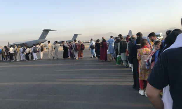 People queue up to board a military aircraft and leave Kabul (Photo: Xinhua/Shutterstock)