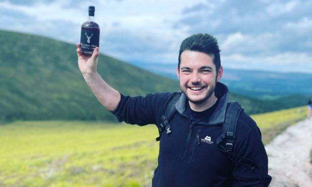 Ellon Gin owner Kieren Murphy proudly holds one of his bottles aloft.