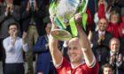 Kinlochshiel captain Keith MacRae lifts the Camanachd Cup (Photo: Neil G Paterson)