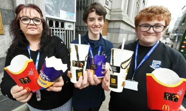 Ryan Bannerman, 15 and Lucas Mackenzie, 14 have launched a charity appeal for people to donate their McDonald's Monopoly Tokens, which give away prizes, including free food and drink. They will donate all the tokens they collect to The Care Hub Aberdeen, which is a local cause which provides support to the vulnerable and homeless. Pictured are Lucas (centre) and Ryan with Michelle Houghton, co-founder of the Care Hub Aberdeen.  Picture by Chris Sumner/DCT