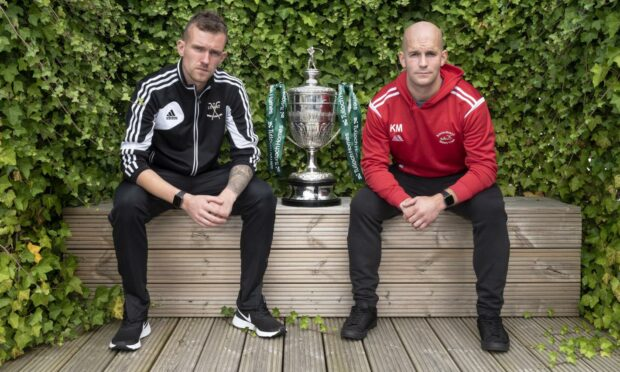 Lovat captain, Stuart MacDonald (left) and Keith MacRae, Kinlochshiel captain, sit either side of the Tulloch Homes Camanachd Cup ahead of this Saturday's 125th Anniversary final at Mossfield, Oban.