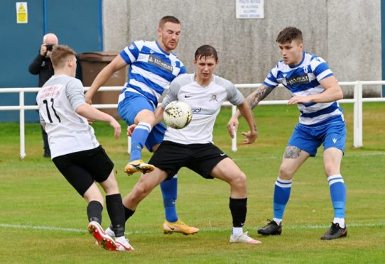 Culter's Nicky Wozniak with the ball, surrounded by Dyce defenders. Picture by Kenny Elrick
