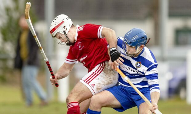 Finlay Macrae (Kinlochshiel) battles with Iain Robinson (Newtonmore).