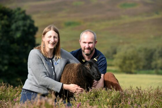Sabrina and George Ross with one of their black Cheviot sheep.