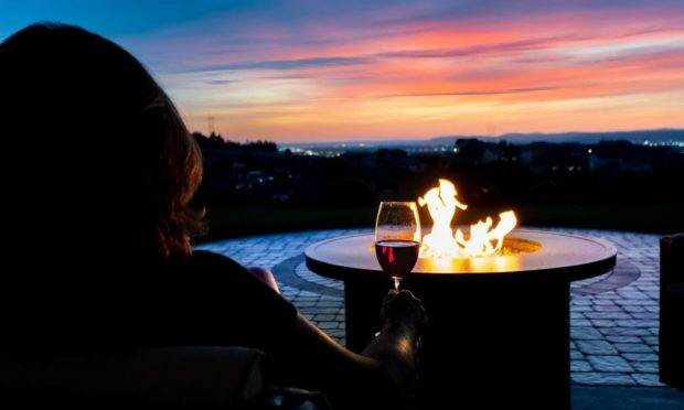 Relaxing by a fire pit with a glass of wine is one of life's great pleasures.