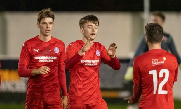 Gregor MacDonald (centre) celebrates netting for Brora Rangers against Rothes.