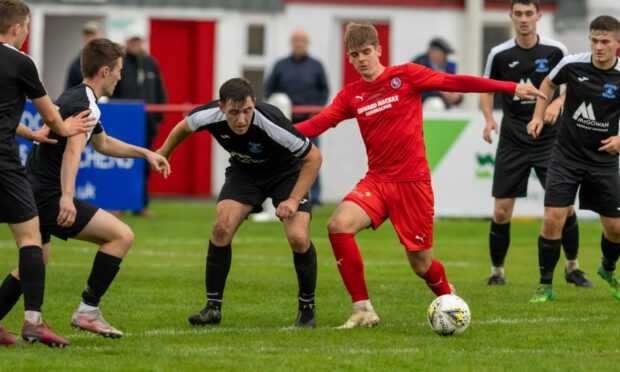 Brora's Matthew Wright, in red, tries to evade Strathspey defenders