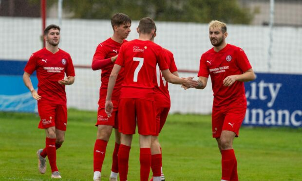 The Brora players celebrate their first goal against Strathspey Thistle