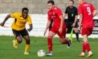 Lossiemouth's Ryan Stuart, centre, looks to get away from a Fort William player