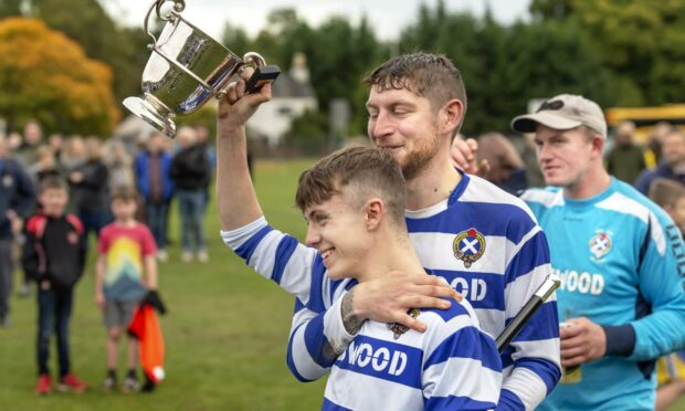 Newtonmore captain Sorley Thomson goes to share the Sutherland Cup with his team.