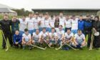 The victorious Skye Camanachd team in the pouring rain at the end of the game.