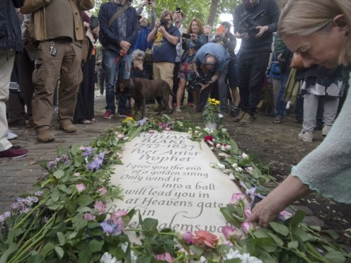 A woman lays a flower by a headstone for William Blake at Bunhill Fields in London (Victoria Jones/PA)