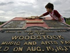 A girl playing on a memorial at the site of the Woodstock Music and Arts Fair in Bethel, New York (Mike Groll/AP)