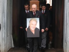A mourner watches as the coffin of comedian Freddy Starr is driven away following his funeral (Peter Byrne/PA)