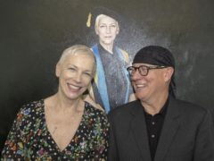 Annie Lennox with artist Gerard Burns (right) in front of the portrait (GCU/PA)