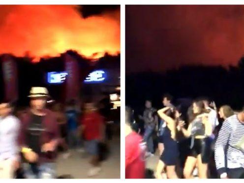 Festival-goers evacuate as the fire burns near the site (shh360/PA)