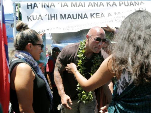 """Actor Dwayne """"The Rock"""" Johnson visits with kupuna, an honoured elder, during a visit to the protest site blocking the construction of the TMT telescope (Jamm Aquino/Honolulu Star-Advertiser/AP)"""