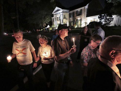 A procession of fans passes by Graceland while visiting Elvis Presley's grave (Jim Weber/AP)