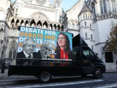 An advertising van showing Prime Minister Boris Johnson, Labour Party leader Jeremy Corbyn and Liberal Democrat leader Jo Swinson, outside the Royal Courts of Justice, London (Isabel Infantes/PA)