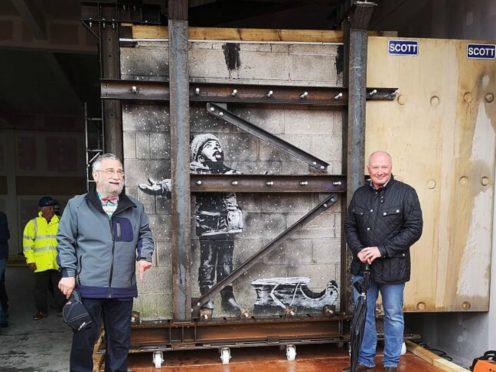 Art dealer John Brandler (left), with garage owner Ian Lewis, as Banksy's Season's Greetings mural (Adam Hale/PA)