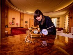 English Heritage Collections curator Olivia Fryman gives a recently donated 1930s gold telephone a final brush up before it goes on public display for the first time at Eltham Palace (English Heritage)